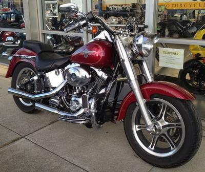 2004 Harley Davidson Fatboy motorcycle with slotted six spoke wheels, a diamond plate theme, handgrips foot A. and foot controls, Screamin Eagle air cleaner, straight exhaust pipes, a mustache engine guard, a detachable passenger backrest and a windscreen