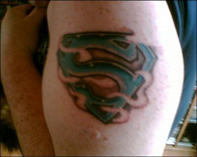 My Superman emblem tattoo is inked on my bicep in blue ink surrounded with