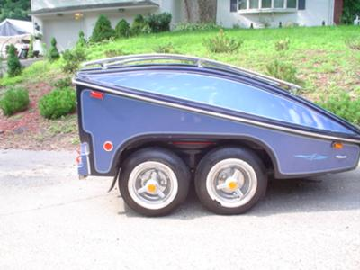 THE DUAL AXLE TRAILER HAS A CUSTOM FITTED COVER